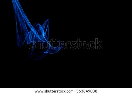 Light painted glowing abstract blue curved lines on a black background - stock photo