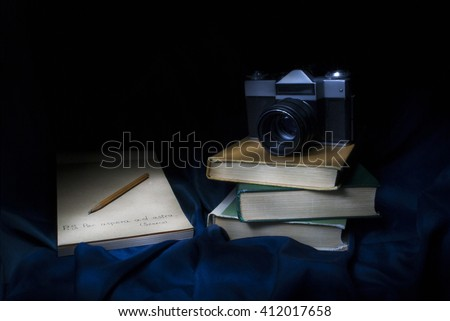"Light painting photo of old camera on books and notebook with quote ""Per Aspera ad Astra"" (english translate ""To the stars through difficulties"")"