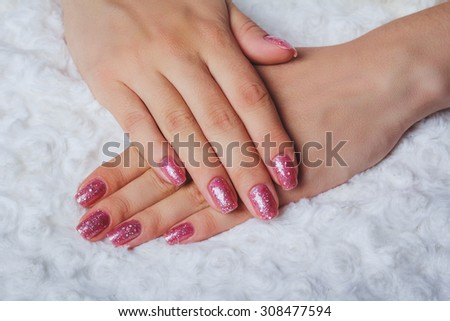 Light pink nail art with tinsel on white background