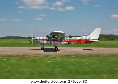 Light plane moving fast along the runway - stock photo