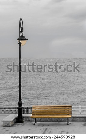Light pole with colored bench on seafront, seaside, cloudy day, dawn. - stock photo