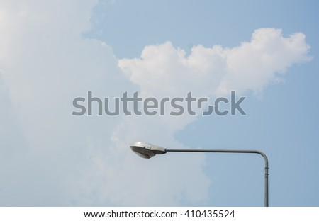 Light poles at the roadside. Lined the streets. Under the sky covered with white clouds.