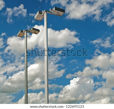 Light poles with a blue sky and clouds.