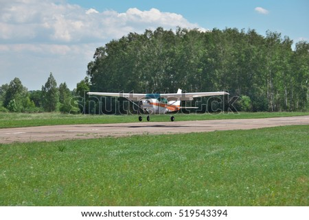Light private plane is landing to the runway of a small airfield on a sunny summer day