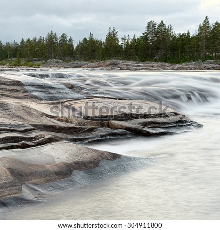 Light rapid stream with bright blurred blue waves. Big boulders in clear water of mountain river. - stock photo