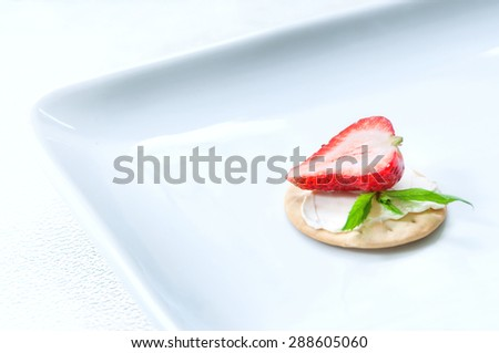 Light snack of water cracker sandwich with cream cheese, ripe fresh strawberry half and mint leaves served on a white square plate. Light white background, selective focus, copy space