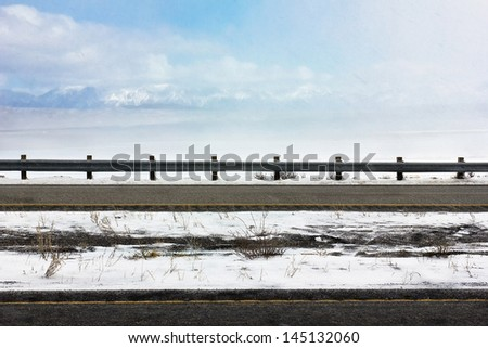 Light snow fall blows across the highway due to some strong winds.  - stock photo