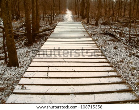 Light snow over a wooden boardwalk on an Illinois hiking trail - stock photo