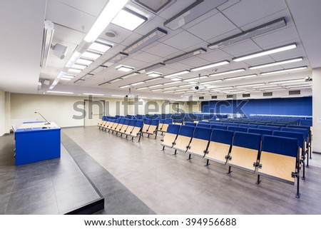 Light, spacious auditorium with blue details, wood chairs and desk - stock photo