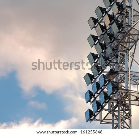 Light stadium sports lighting against on blue sky background. - stock photo