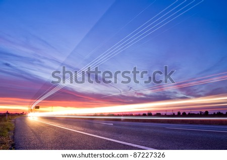 light streaks from long exposure of traffic at sunset - stock photo