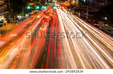 light streams from ongoing traffic in business district road. - stock photo