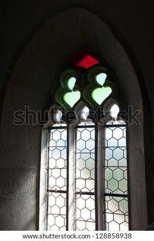light streams through stained glass window inside a church - stock photo