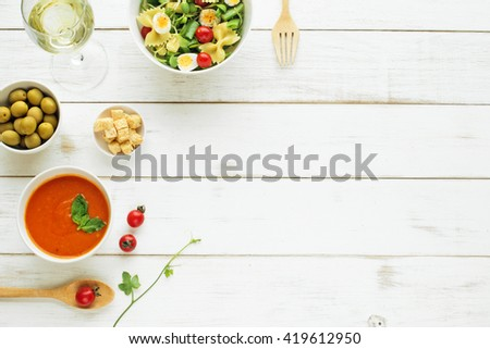 Light summer dinner / supper concept. Green salad with pasta, cherry tomato, quail eggs. Cold tomato soup (gazpacho), green olives and glass of cold white wine.  - stock photo