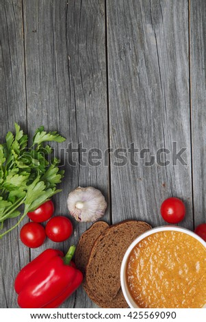 Light summer meal concept. Cold tomato soup (gazpacho) with croutons on a wooden table. Copy space. - stock photo