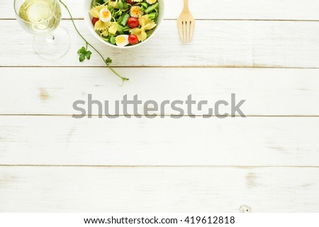 Light summer meal concept. Green salad with pasta, cherry tomato, quail eggs and glass of white wine on a white table. Copy space. - stock photo