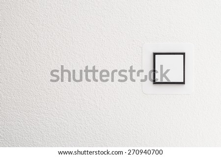 Light switch on white wall, detail shot with copy space - stock photo