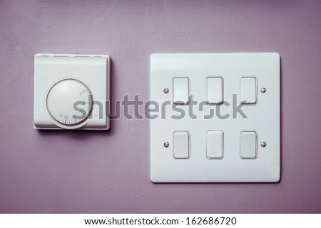 Light switches and thermostat - stock photo