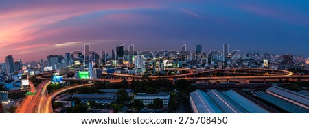 Light tail of Transportation car on road way at night life and Business Building Bangkok city area background as panorama, high angle birds eye view - stock photo