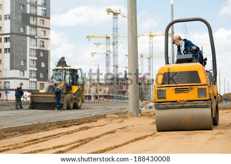 Light tandem vibratory roller compacting sand or soil during construction workers with shovels and tractor vehicle preparation road surface before laying an asphalt driveway - stock photo