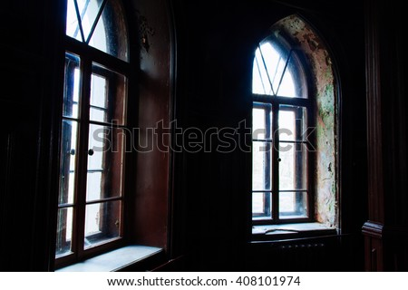 Light through the old wooden windows in an abandoned building dark gloomy - stock photo