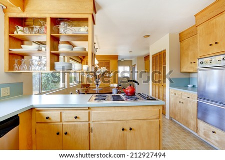 Light tone kitchen cabinets with mint color top and built-in stove - stock photo