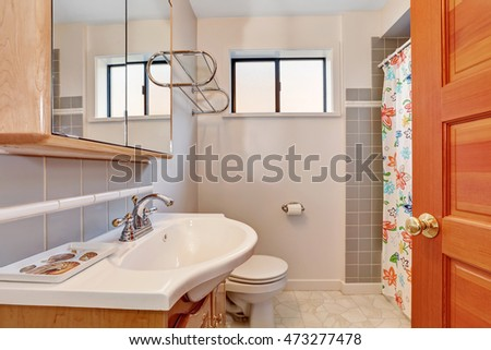 Light tones bathroom interior with grey tile wall trim, floral patterned shower curtain and vanity cabinet with sink. Northwest, USA