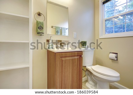 Light tones bathroom with french window. View of washbasin cabinet, toilet and built-in shelves