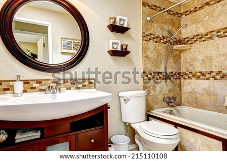 Light tones bathroom with tile wall trim. Wooden vanity cabinet with white sink and round mirror - stock photo