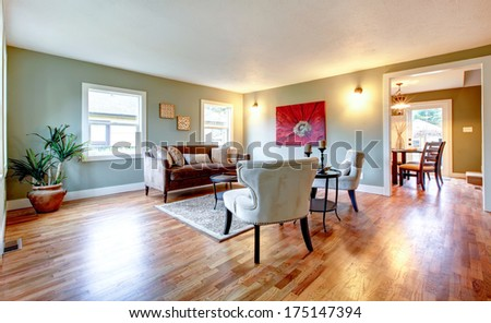 Light tones big living room furnished with antique style sofa and chairs. Palm pot and hardwood floor create exotic theme - stock photo