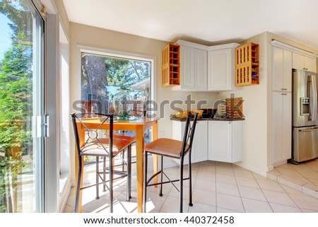 Light tones dining room with brown table set, white cabinets and tile floor. View of kitchen room with stainless steel fridge. - stock photo