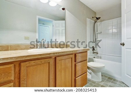 Light tones empty bathroom with tile floor, white bath tub and wooden vanity cabinet