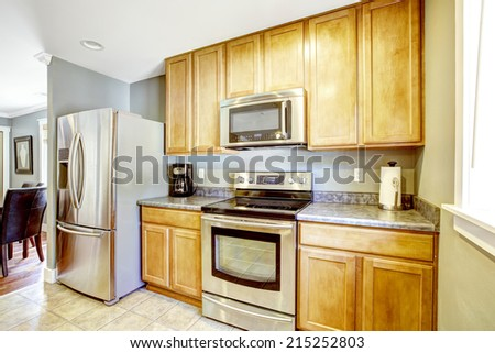 Light tones kitchen cabinets with granite top and steel appliances