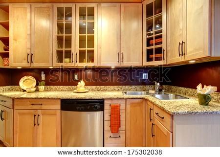 Light tones kitchen storage combination with burgundy backsplash and steel stove - stock photo