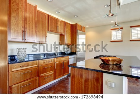 Light tones modern kitchen room with cherry tile floor and whiskey color wooden kitchen cabinets - stock photo