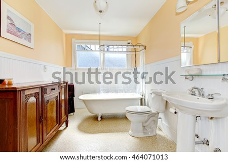 Light tones small bathroom with a whiskey color antique cabinet. Northwest, USA