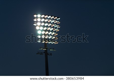 Light tower lit at a stadium during nightime.