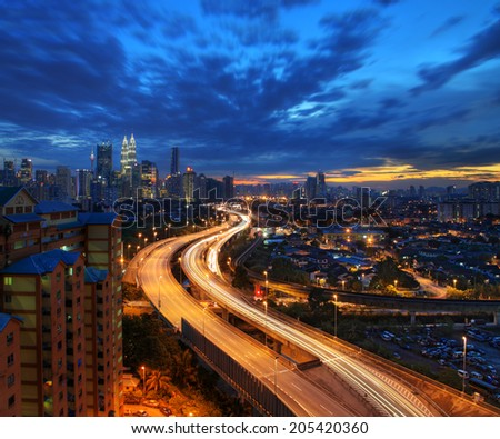 Light trail at busy highway with the view of Kuala Lumpur city - stock photo