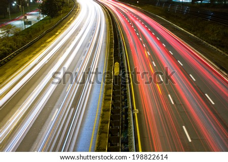 Light trail on a busy motorway high angle - stock photo