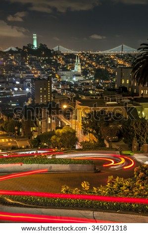 Light trails down Lombard St with Coit Tower and Telegraph Hill in the distance