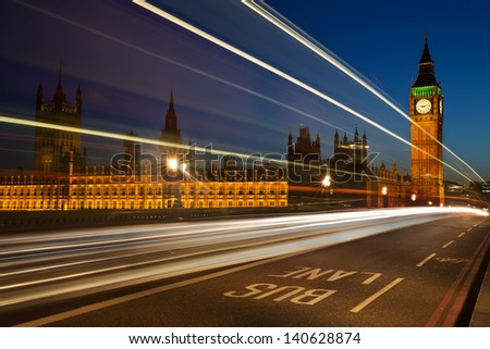 Light trails from London buses and vehicles with the Elizabeth Tower (Big Ben) of the Palace of Westminster in the background and the words Bus Lane in the foreground - stock photo