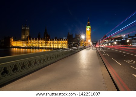 Light trails from London buses and vehicles with the Elizabeth Tower (Big Ben) of the Palace of Westminster in the background and the path on Westminster bridge foreground