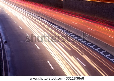 light trails of moving cars on city street - stock photo