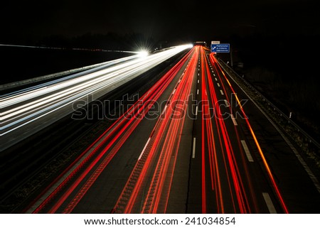 Light trails on a german Autobahn (Highway) at the motorway exit Pfaffenhofen. - stock photo