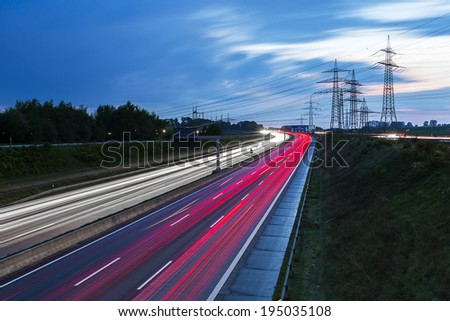 Light trails on a highway freeway at sunset with power Pylons in the background - stock photo