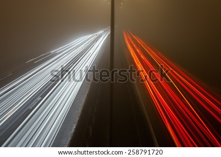 Light trails on the four lane highway at a foggy night - stock photo