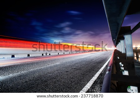 Light trails on the road to the side of the guard rail - stock photo