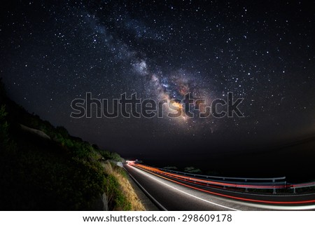 Light trails on the road with the milky way galaxy on the sky (horizontal)  - stock photo
