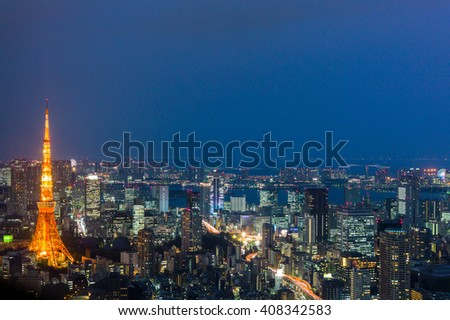 Light up Tokyo Cityscape  view with Tokyo Tower at left of picture after sunset surrounded by other buildings in Tokyo, Japan