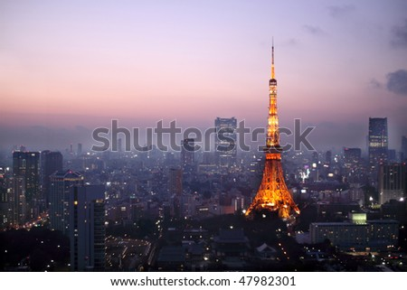 Light up Tokyo Tower during sunset surrounded by other buildings in Tokyo, Japan - stock photo